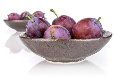 Lot of whole fresh blue plum in a dark ceramic bowl isolated on white background