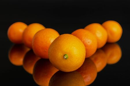 Group of seven whole fresh orange kumquat arranged symmetrically isolated on black glass