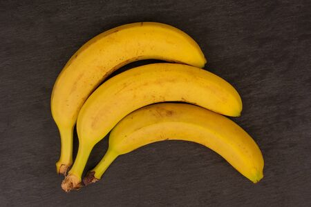 Group of three whole ripe yellow banana flatlay on grey stone