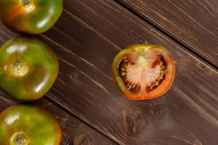 Group of three whole one half of fresh greenish red tomato flatlay on brown wood