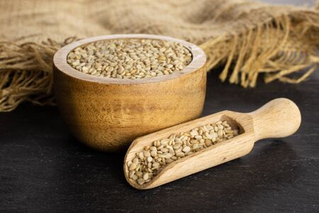 Lot of whole unpeeled sesame seeds in wooden bowl with wooden scoop on jute cloth on grey stone