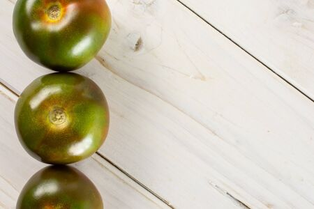 Group of three whole fresh greenish red tomato copyspace on right flatlay on white wood