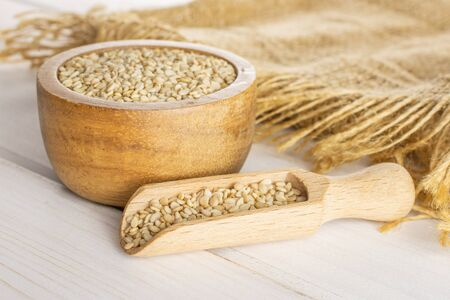 Lot of whole unpeeled sesame seeds in wooden bowl with wooden scoop on jute cloth on white wood Banque d'images