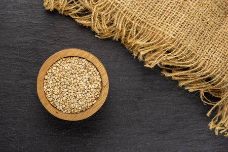 Lot of whole unpeeled sesame seeds in wooden bowl on jute cloth flatlay on grey stone