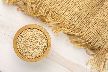 Lot of whole unpeeled sesame seeds in wooden bowl on jute cloth flatlay on white wood