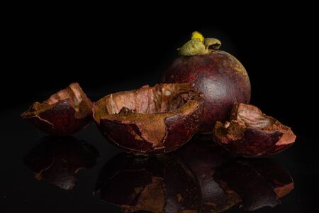 Group of one whole three pieces of deep purple mangosteen hollow skin isolated on black glass