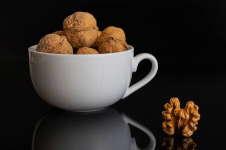 Lot of whole ripe brown walnut one is aside without shell and the rest is in white ceramic cup isolated on black glass