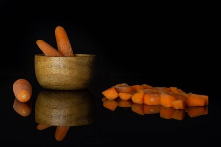Group of three whole lot of pieces of stale  orange stale baby carrot baby in wooden cup isolated on black glass Reklamní fotografie