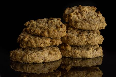 Group of six whole oat crumble biscuit isolated on black glass Stock Photo