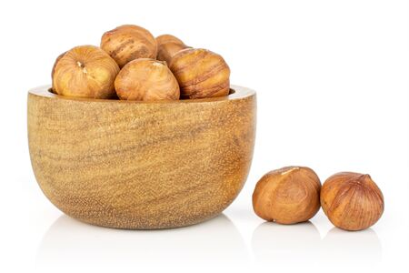 Lot of whole ripe brown hazelnut two are aside and rest is in tiny wooden bowl isolated on white background Imagens