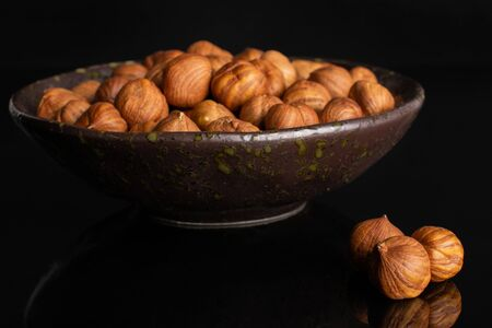 Lot of whole ripe brown hazelnut three are in front and rest is in dark ceramic bowl isolated on black glass