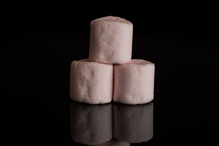 Group of three whole pink sweet fluffy marshmallow isolated on black glass