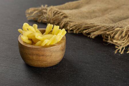 Lot de gemelli de pâtes crues entières dans un bol en bois avec toile de jute sur pierre grise Banque d'images