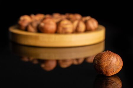 Lot of whole ripe brown hazelnut one is in front and rest is in back on round bamboo coaster isolated on black glass