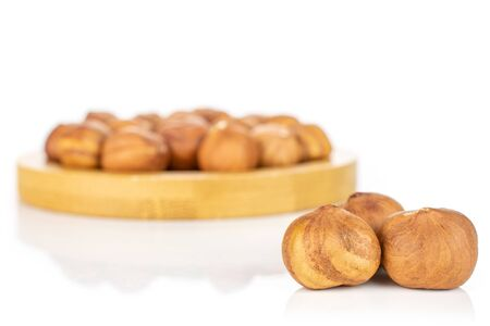 Lot of whole ripe brown hazelnut three are in the front and the rest is in the back isolated on white background Imagens