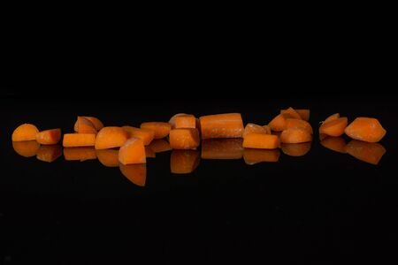 Lot of pieces of stale  orange stale baby carrot baby isolated on black glass