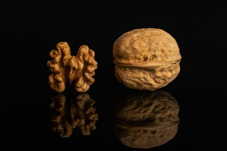 Group of two whole ripe brown walnut one is with shell isolated on black glass Imagens