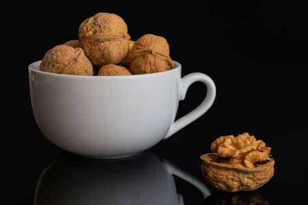 Lot of whole ripe brown walnut one is aside and the rest is in white ceramic cup isolated on black glass