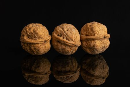 Group of three whole ripe brown walnut in row isolated on black glass Imagens