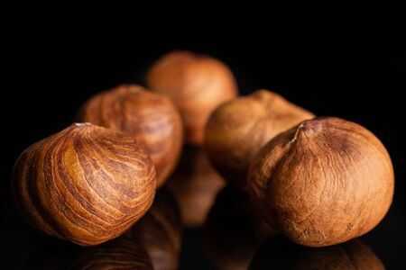 Group of five whole ripe brown hazelnut arranged symmetrically in closeup isolated on black glass 版權商用圖片 - 128574861