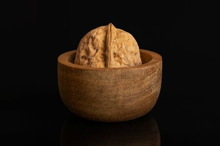 One whole ripe brown walnut in tiny wooden bowl isolated on black glass
