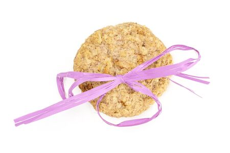 One whole oat crumble biscuit with violet ribbon flatlay isolated on white background