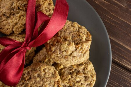 Lot of whole oat crumble biscuit with crimson ribbon on grey ceramic plate flatlay on brown wood