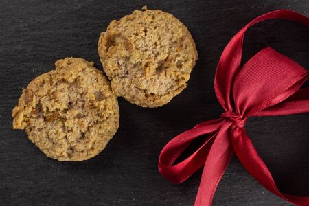 Group of two whole oat crumble biscuit with crimson ribbon flatlay on grey stone
