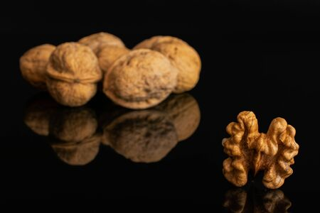 Lot of whole ripe brown walnut one is in the front without shell isolated on black glass Imagens