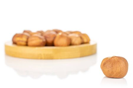 Lot of whole ripe brown hazelnut one is in front and rest is in back on round bamboo coaster isolated on white background