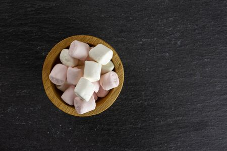 Lot of whole sweet fluffy marshmallow copyspace in wooden bowl flatlay on grey stone Imagens