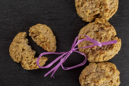 Group of three whole two halves of oat crumble biscuit with violet ribbon flatlay on grey stone