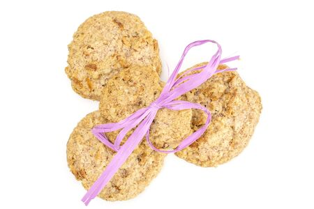 Group of four whole oat crumble biscuit with violet ribbon flatlay isolated on white background