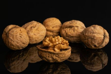Group of six whole ripe brown walnut arranged symmetrically isolated on black glass Imagens