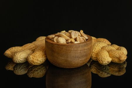 Lot of whole lot of halves of natural yellow peanut in tiny wooden bowl isolated on black glass