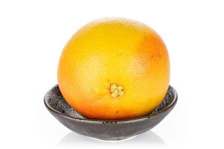 One whole fresh pink grapefruit in dark ceramic bowl isolated on white background