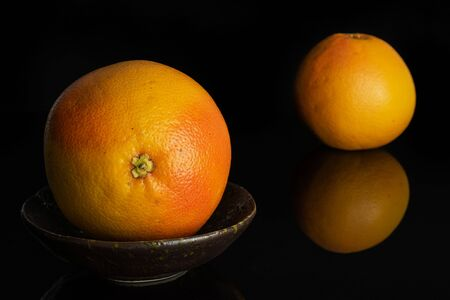 Group of two whole fresh pink grapefruit one is aside in dark ceramic bowl isolated on black glass