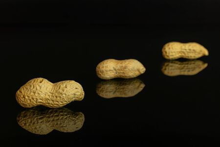 Group of three whole natural yellow peanut placed diagonally in line isolated on black glass Imagens