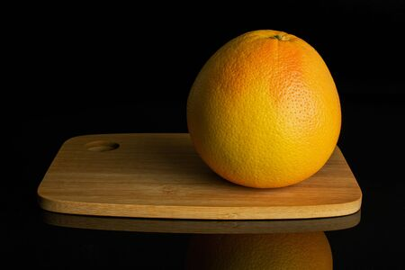 One whole fresh pink grapefruit on bamboo cutting board isolated on black glass
