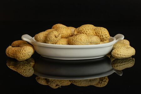 Lot of whole natural yellow peanut in white oval ceramic bowl isolated on black glass Imagens