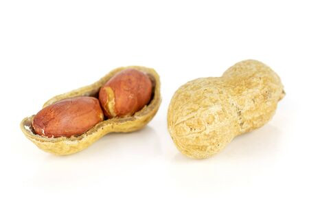 Group of two whole natural yellow peanut one is open in closeup isolated on white background