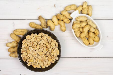 Lot of whole lot of halves of natural yellow peanut in white oval ceramic bowl in dark ceramic bowl flatlay on white wood