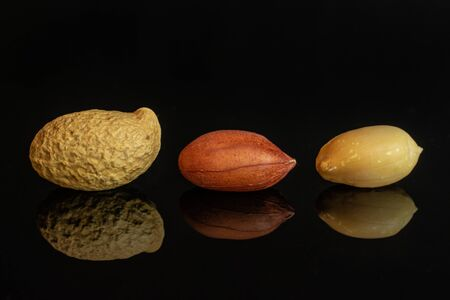 Group of three whole natural yellow peanut in row isolated on black glass