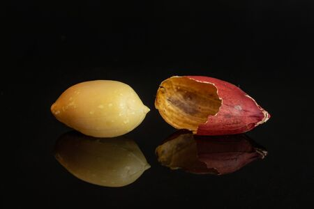 Group of one whole one piece of natural yellow peanut skin is aside in closeup isolated on black glass