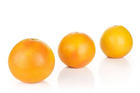 Group of three whole fresh pink grapefruit placed diagonally in line isolated on white background Imagens