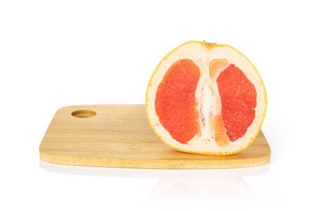 One half of fresh pink grapefruit on bamboo cutting board isolated on white background Imagens