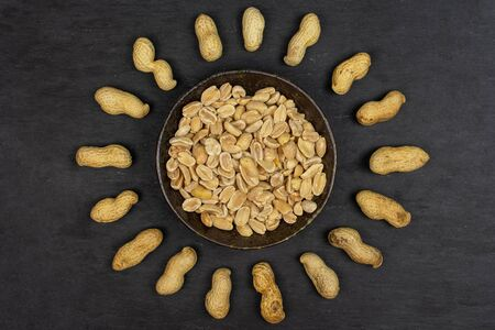Lot of whole lot of halves of natural yellow peanut in dark ceramic bowl flatlay on grey stone