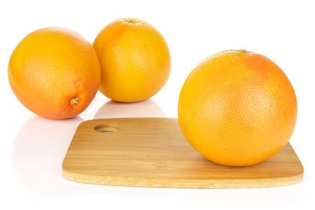 Group of three whole fresh pink grapefruit on bamboo cutting board isolated on white background Imagens