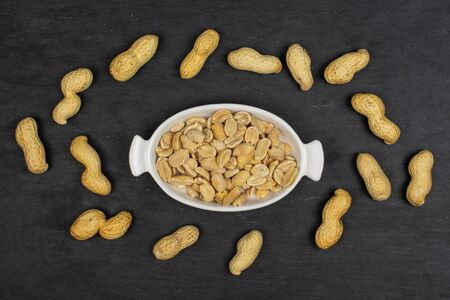 Lot of whole lot of halves of natural yellow peanut in white oval ceramic bowl flatlay on grey stone Imagens