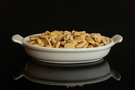 Lot of halves of natural yellow peanut in white oval ceramic bowl isolated on black glass